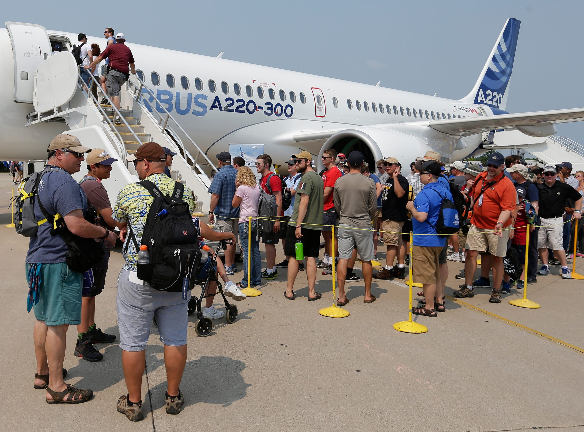 Spectators wait in line to get a look at the AirBus A220-300 which flew into AirVenture 2018. The first day of AirVenture 2018 opened on July 23, 2018.  Thousands of people will pass through the gates of AirVenture.