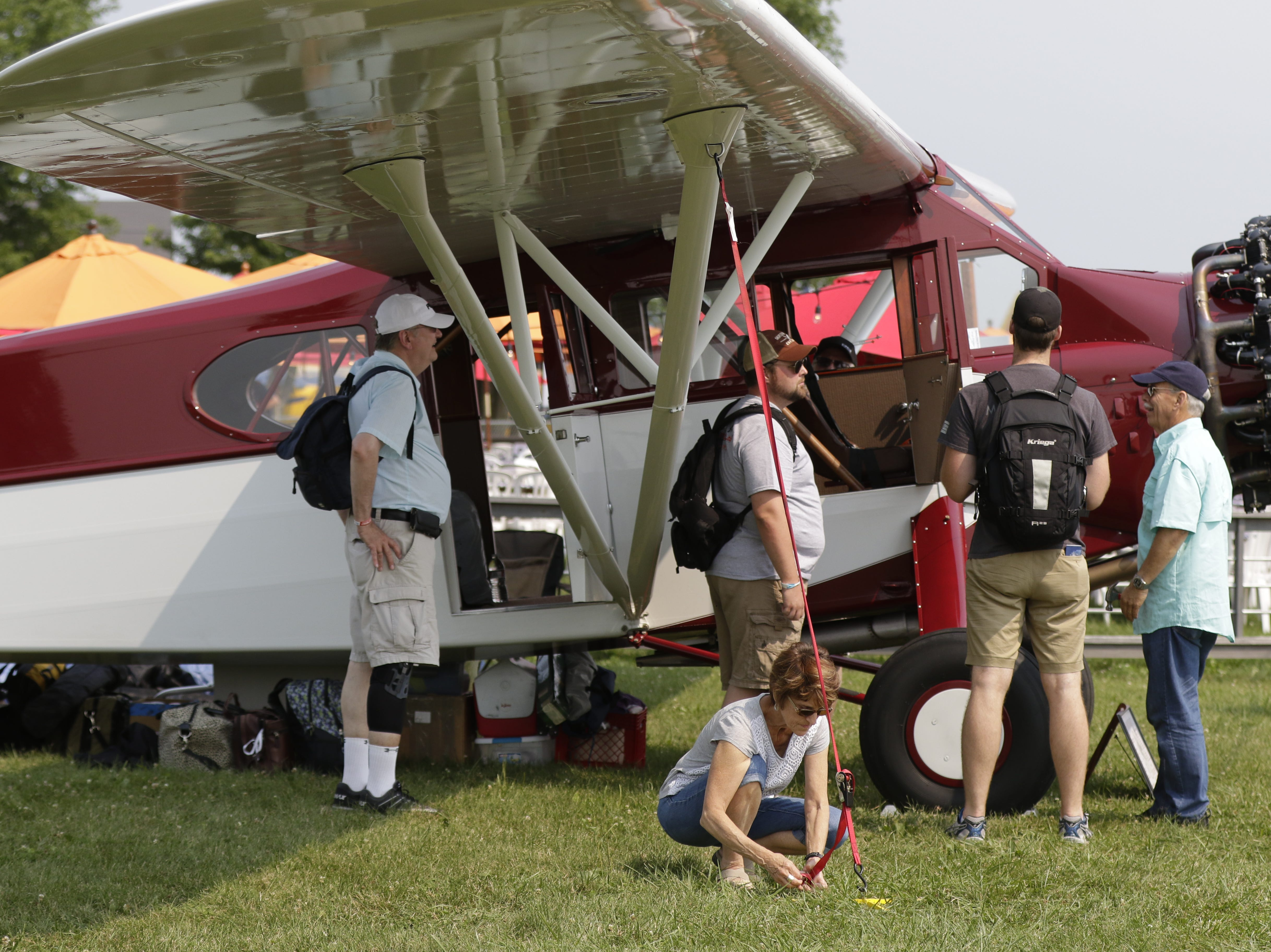 Jeanie Horst of Smoketown, PA, ties down a Fairchild 71 in the Vintage area of AirVenture.  The first day of AirVenture 2018 opened on July 21, 2018.  Thousands of people will pass through the gates of AirVenture.