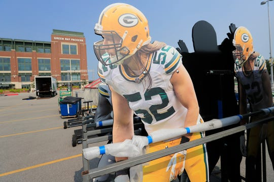 Life-sized Clay Matthews figures are shown as setup work for the Packers Experience continues outside Lambeau Field on Monday, July 23, 2018 in Green Bay, Wis. The Packers Experience is free to attend and will be open for fans from July 26-29.
