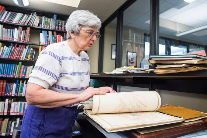 Wendy Bish-McGrew flips through a book containing maps of the townships and boroughs of Adams County from 1872 inside the Pennsylvania Room at Guthrie Memorial Library.