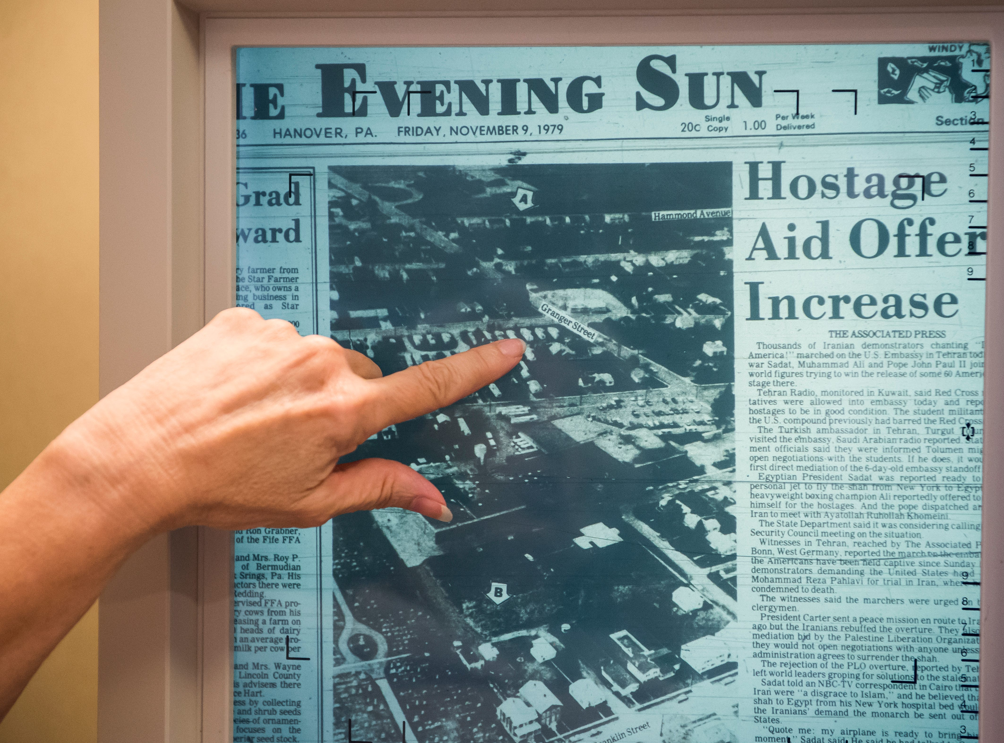Using a microfilm scanner at Guthrie Memorial Library, Wendy Bish-McGrew points out a detail on an article from 1979 that shows the route Holly Carbaugh took the day she was murdered.