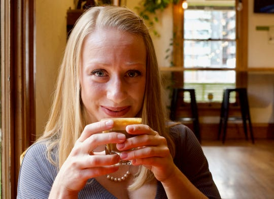 Erin Westgate, owner of Songbird Coffee and Tea House smiles before taking a sip of coffee.