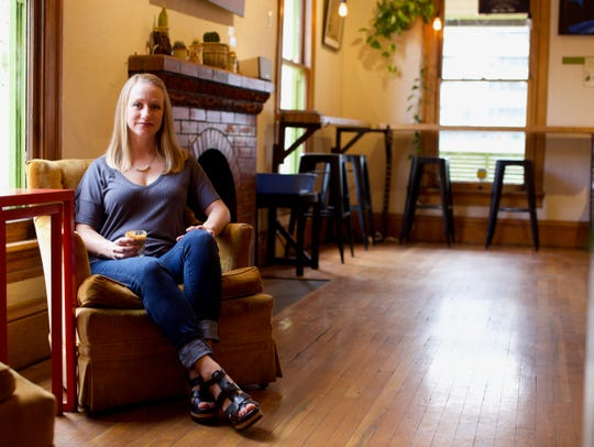 Local small business owner, Erin Westgate, in a cozy chair inside of her coffee and tea house, Songbird.