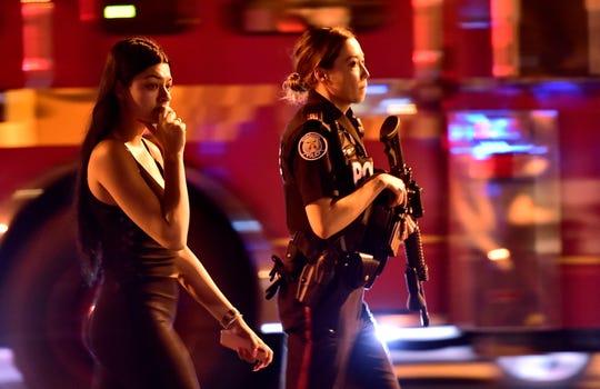 Una agente de la policía escolta a una mujer luego de la balacera.