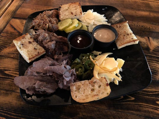 The house-smoked meat board includes smoked brisket, pulled pork and roast beef, plus cheeses, pickles, roasted jalapeños and grilled garlic bread.