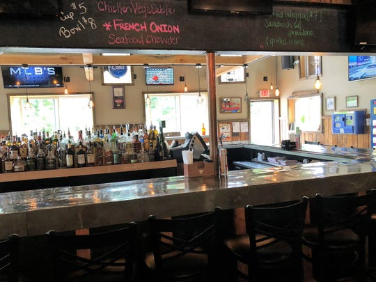 The bar is the center of Ridge Runners Bar and Grill. Food and drink specials are written with chalk on exposed beams.