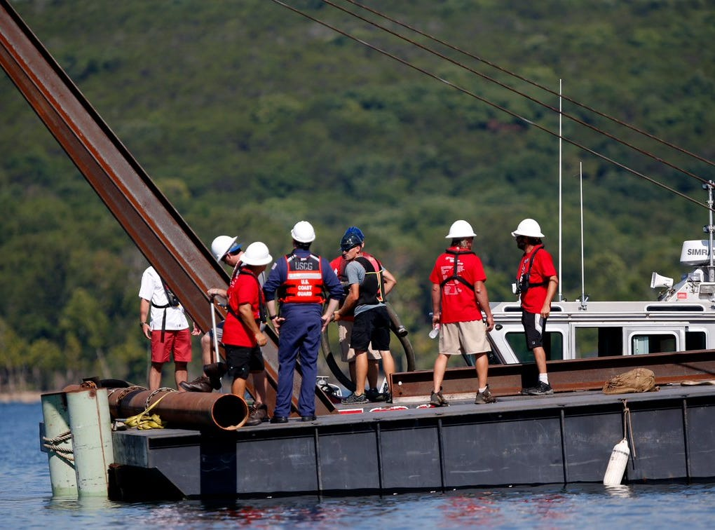 Divers emerge from the water during salvation operations for the duck boat in Table Rock Lake.