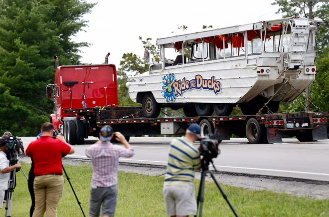 The capsized duck boat is being hauled away on a flatbed trailer down Missouri 265 on Monday, July 23, 2018 in Branson, Mo.
