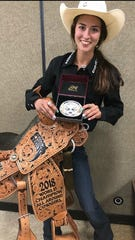McKenna Coronado poses with her prize buckle and saddle