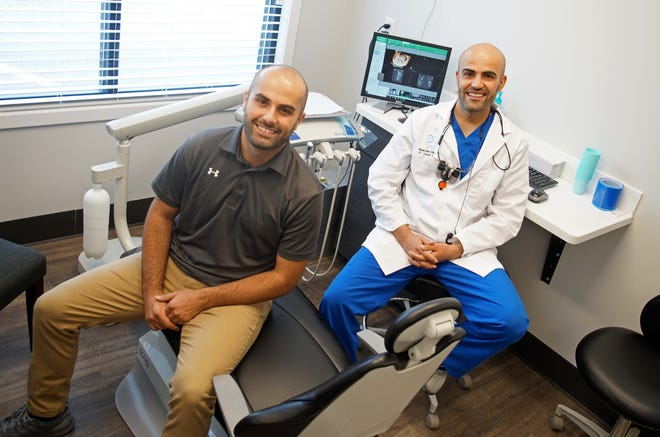 University of Delaware graduate Farhad Baqi, a business manager, sits with his older brother Dr. Seyar Baqi, at the his dental practice, Blue Hen Dental in Smyrna, where they both work together.