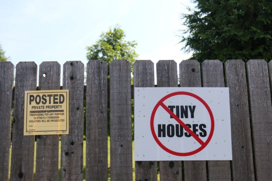 A neighbor posts a sign against the proposed tiny homes for veterans project at Victory Church in Dover. The sign is one of handful posted on about five homes near the church.