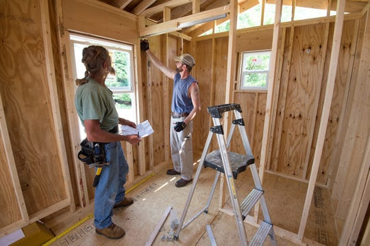 David Wilkins, left, and Jacob Hill work on installing a pocket door for the bathroom area of a tiny house being built for an affordable housing effort in Kent County.