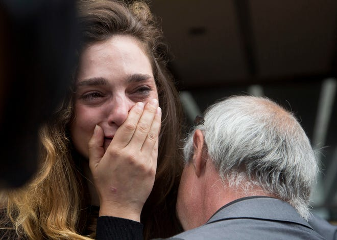 New York Daily News staff reporter Chelsia Rose Marcius cries as she is hugged by staff photographer Todd Maisel after they were both laid off, Monday, July 23, 2018, in New York. The tabloid will cut half of its newsroom staff, saying it wants to focus more on digital news.