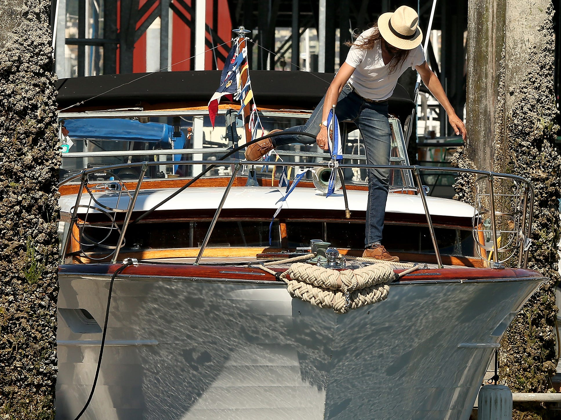 Maurizio Hublitz, of Vancouver BC,  steps over the flags strung across his  1959 32' Express 32 Chris-Craft named Bianca as he fills the water tank during the Chris-Craft Rendezvous at the Port Orchard Marina on Friday, July 13, 2018.