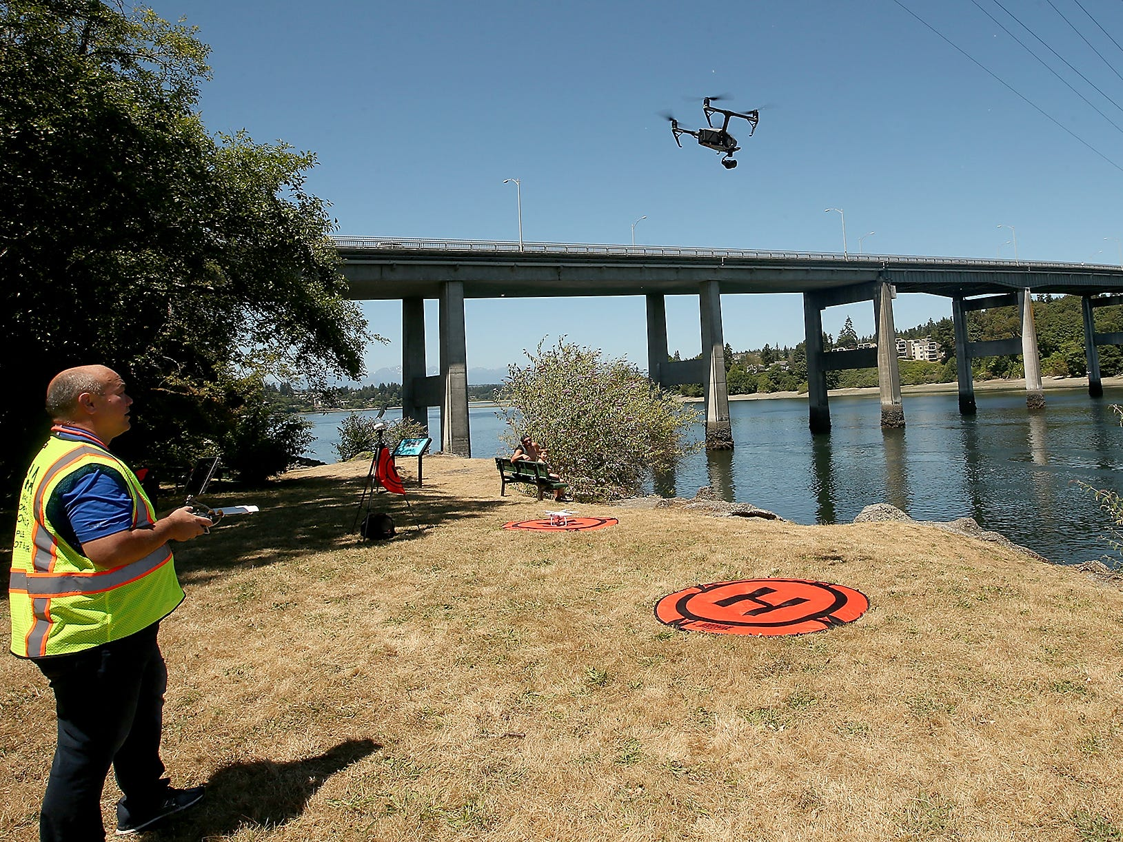 Pacific Northwest Aerial Vision, LLC drone operator James Morton (left) pilots his drone off the landing pad as Sablehawk Drone Inspections pilot Jeff Fuchs (right) works as his spotter while the two fly their drones at Lower Roto Vista Park in Bremerton on Friday, July 13, 2018.