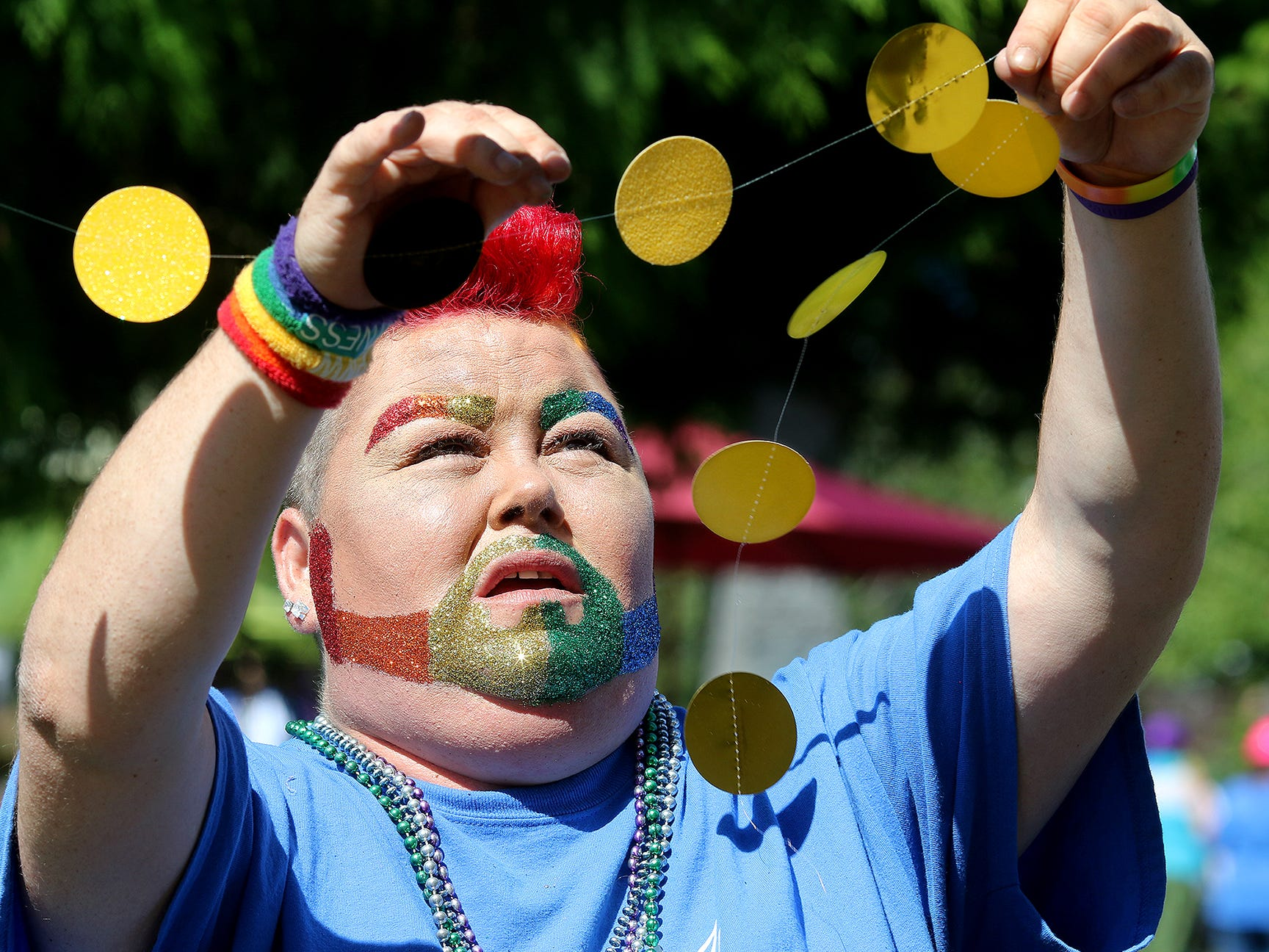 Haley Gregory, of Bremerton, puts out decorations on the Queerly Beloved booth at the Kitsap Pride Festival onSaturday July, 21, 2018 at Evergreen-Rotary Park in Bremerton.