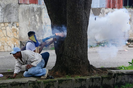 Anti-government protesters fire homemade mortars at police in Jinotepe, Nicaragua last month.