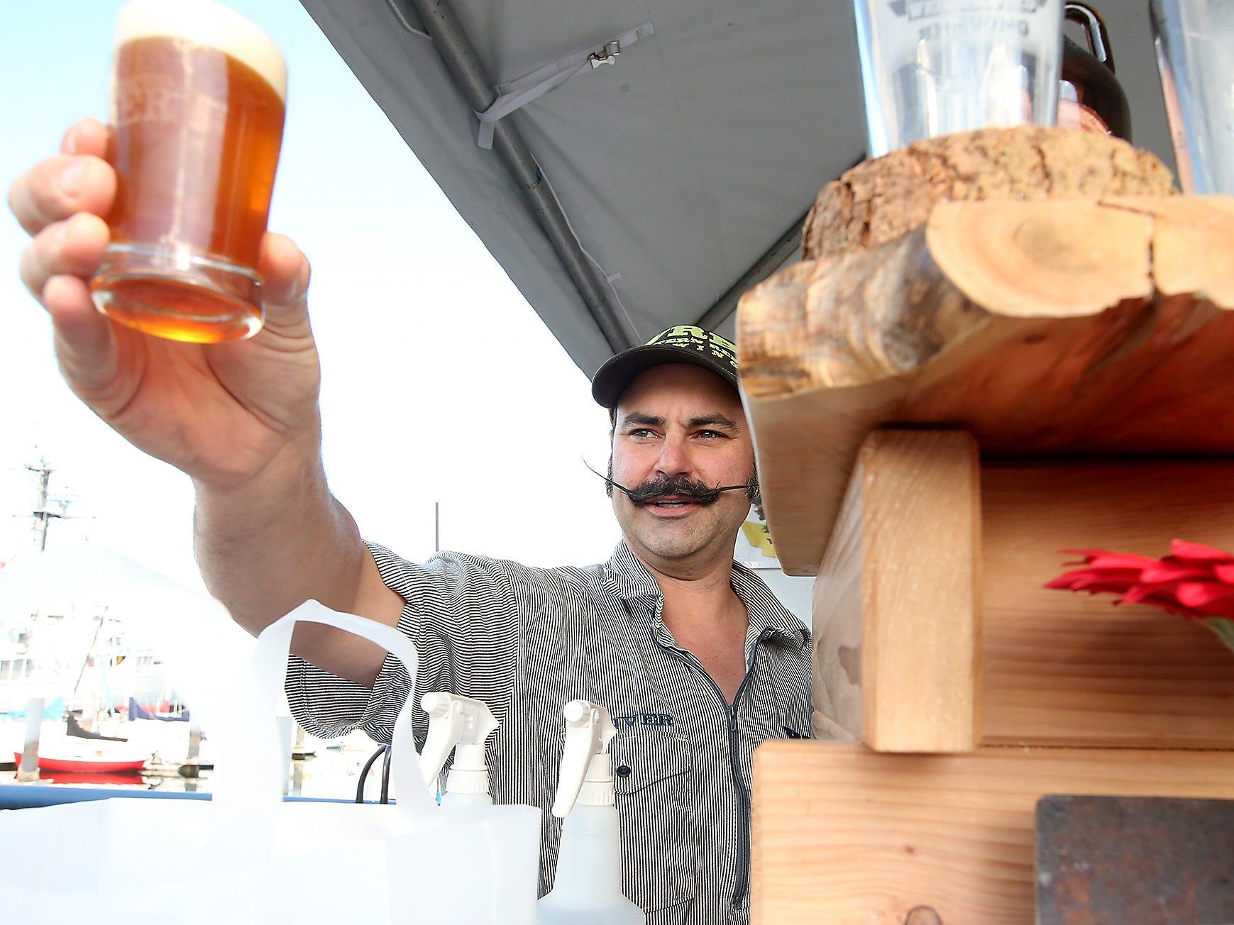 Western Red Brewing's Denver Smyth serves up a beer during the Bremerton Summer Brewfest on the Bremerton Boardwalk on Friday, July 20, 2018.