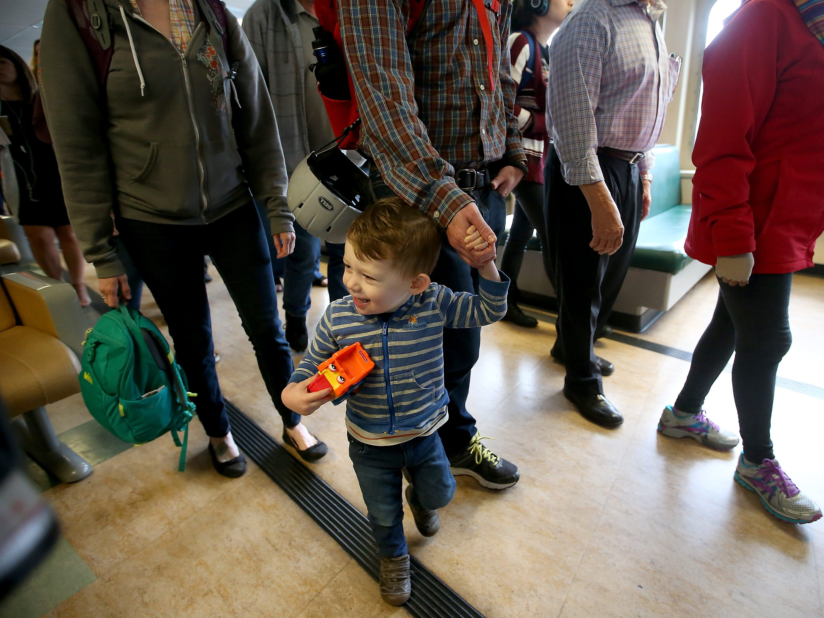 Kellas MacPherson, 2, holds his father Gavin's hand as they make their way off the crowded Washington State Ferry Walla Walla at Coleman Dock in Seattle on Thursday, July 19, 2018.