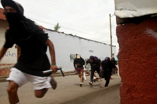 Opponents to the government of Nicaraguan President Daniel Ortega are forced away from their barricade as the government forces enter the city of Masaya, Nicaragua, last month.