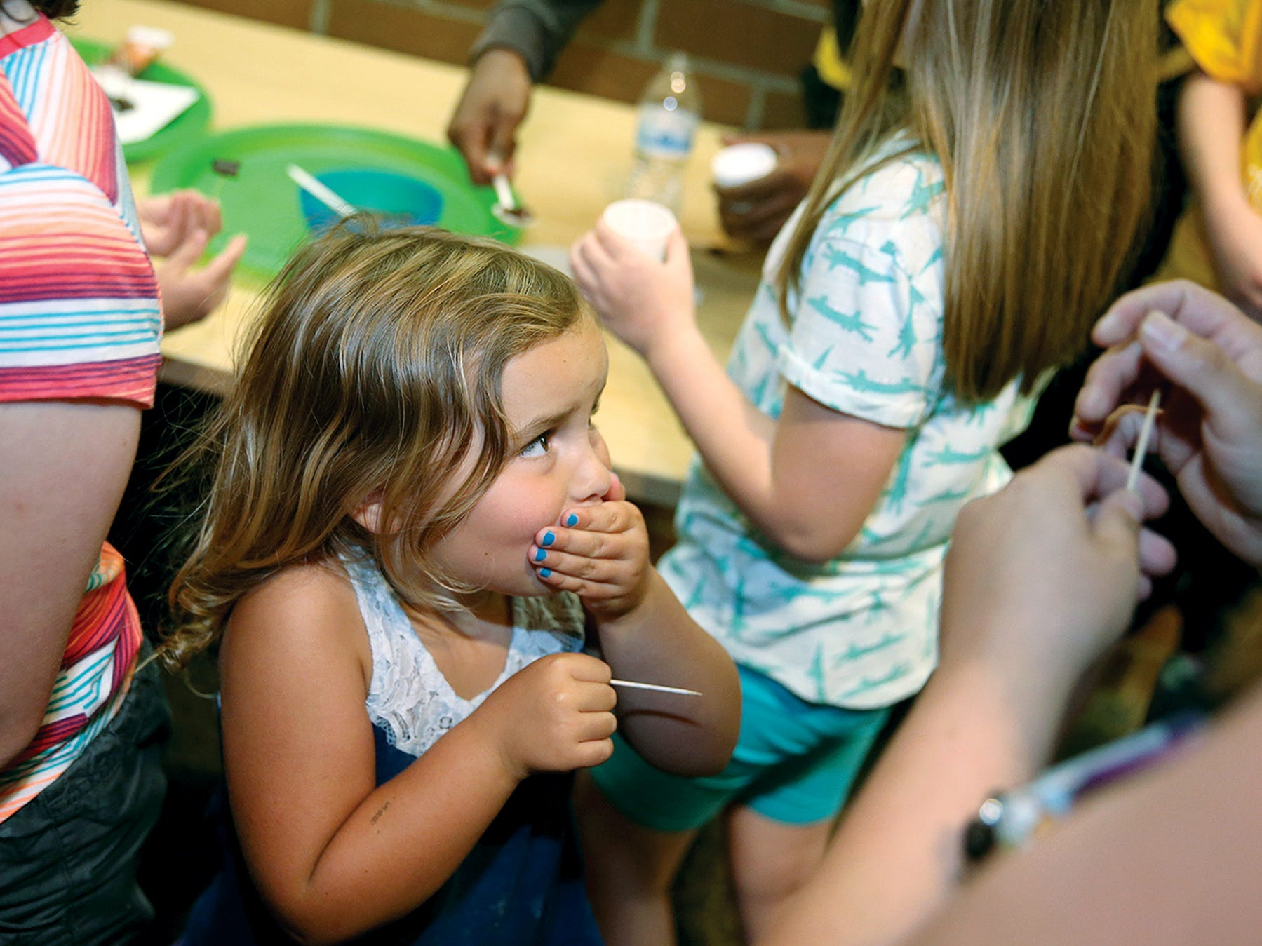 """Devyn Yorba, 5, reacts to the spicy taste of a grasshopper at the Kitsap Regional Library """" The Bug Chef """" presentation at the Central Branch Library in East Bremerton. Kids were offered bugs snacks by bug chef David George Gordon."""