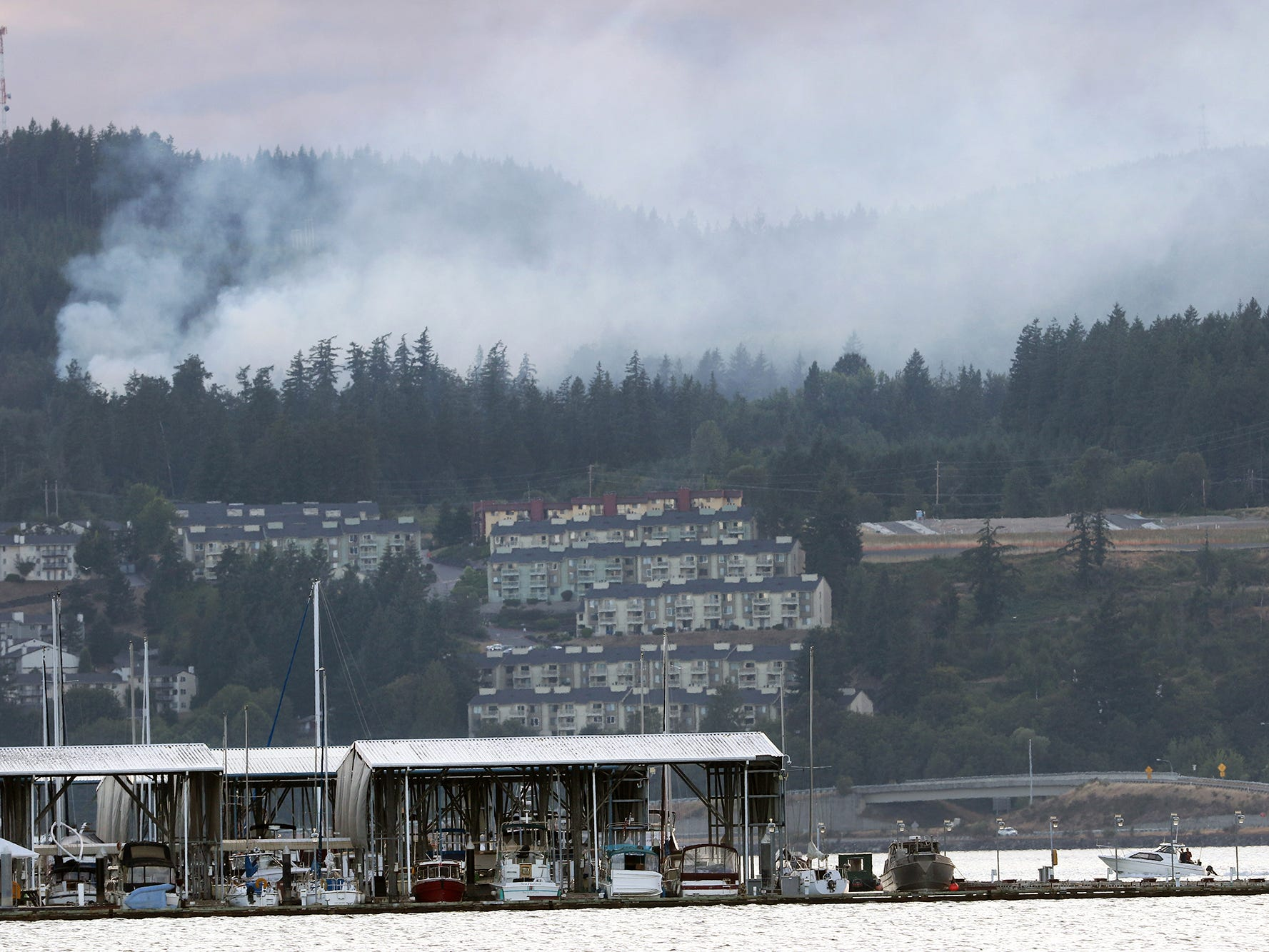 A fire burns in the Bremerton Watershed in a view from Port Orchard towards the marina on Wednesday evening.
