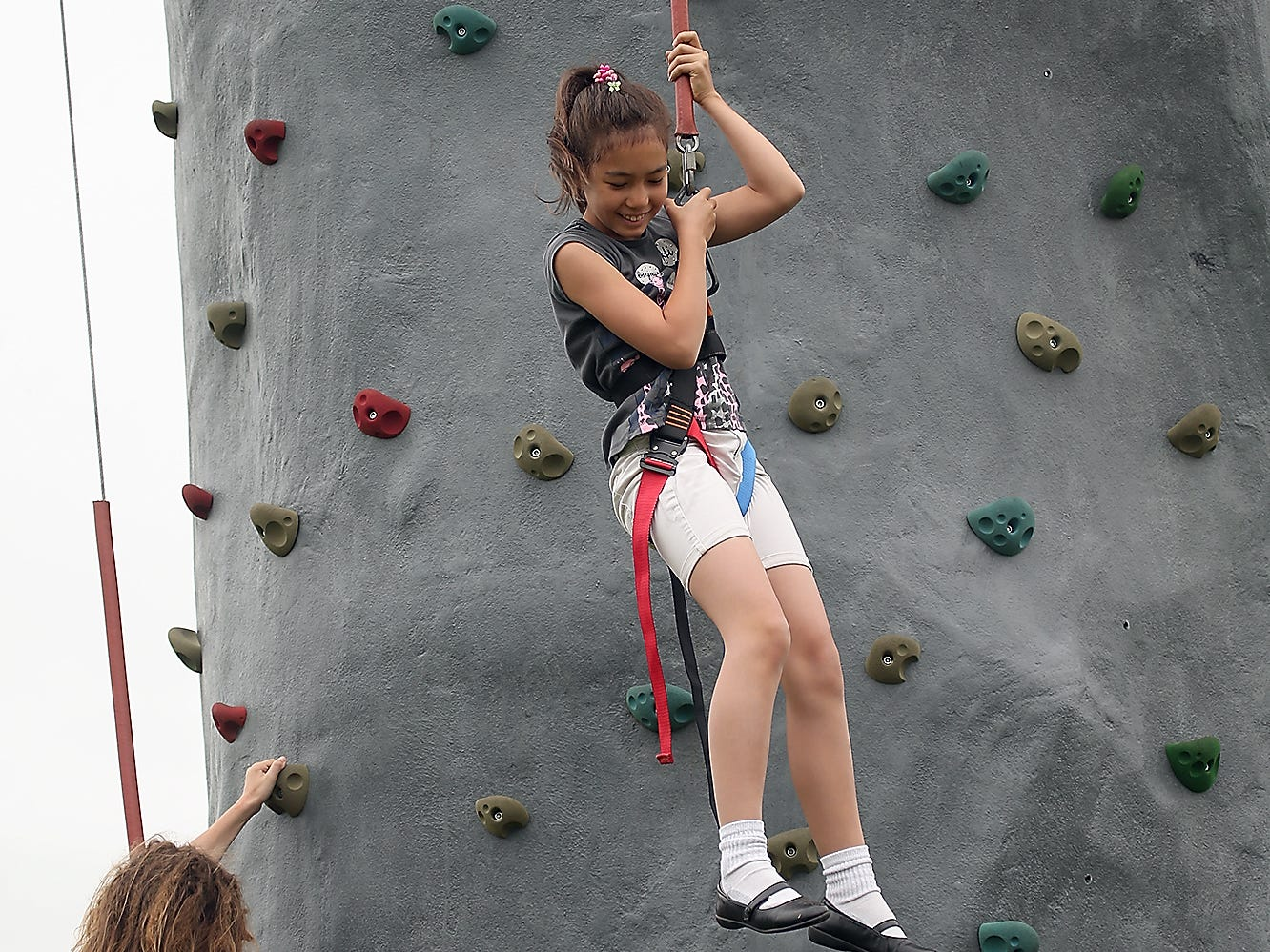 """After her climb to the top of the National Guard climbing wall, Natalie Knez, 10, smiles as she repels to the ground at Bremerton's Kiwanis Park on Wednesday, July 18, 2018. The wall will be at Kiwanis Park Friday, July 20 Tuesday, July 24 and Wednesday, July 25 as part of Bremerton Parks and Recreation's """"Fun at the Playgrounds"""" program."""