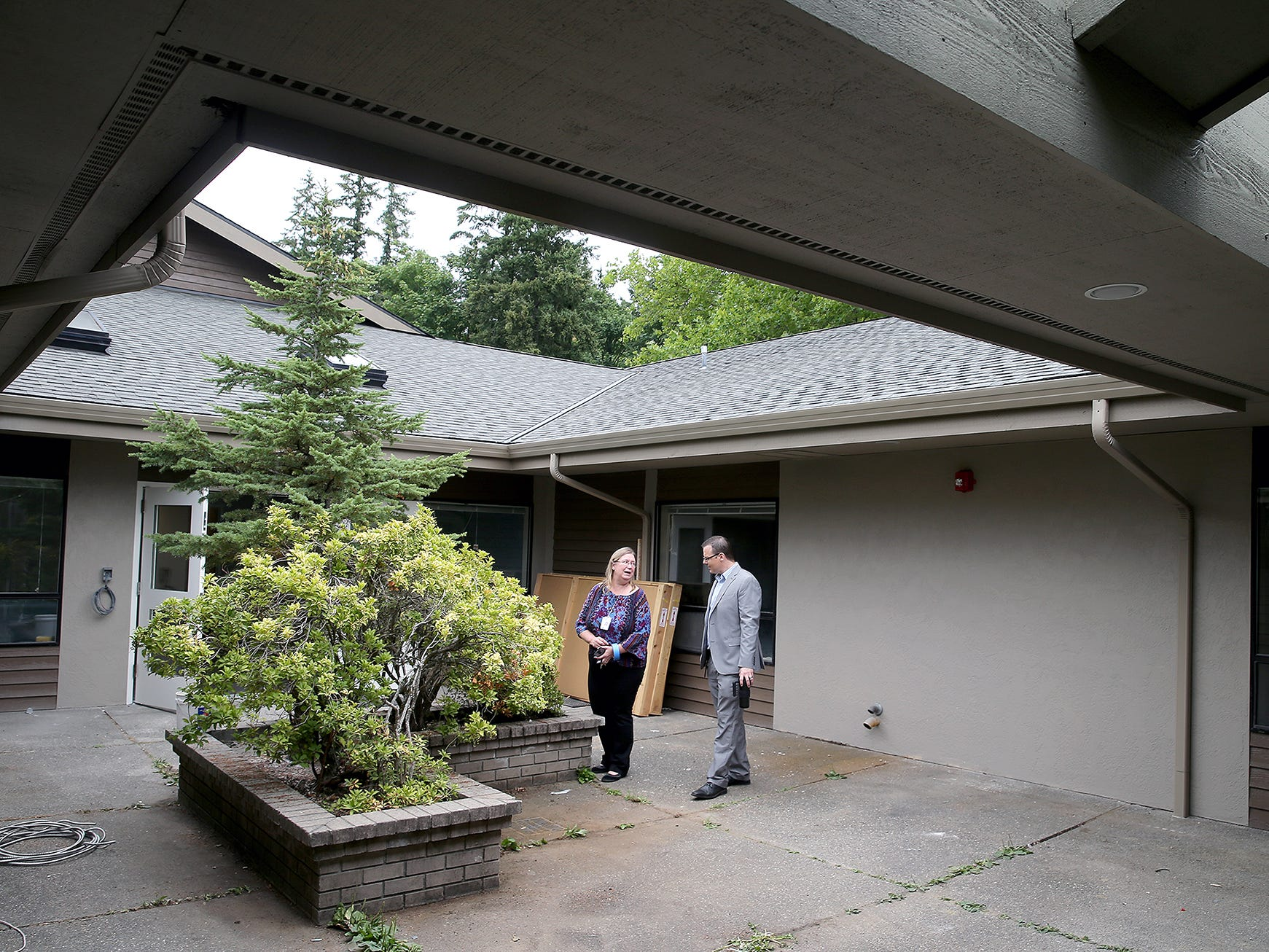 Rochelle Doan, center, Chief Advancement Officer and, Neil Olson Director of 24/7 recovery Services at Kitsap Mental Health Services in the courtyard of the long-awaited crisis triage center in East Bremerton.