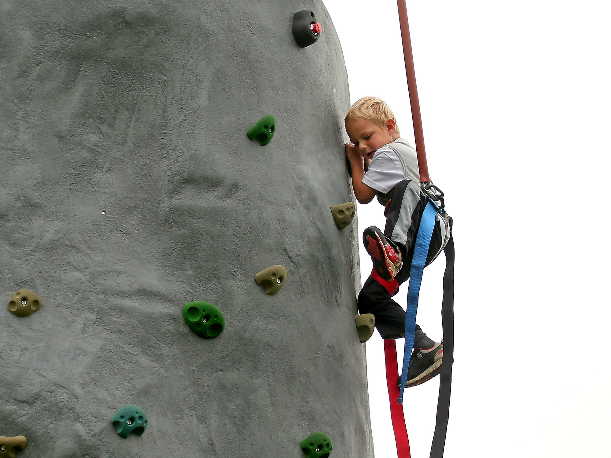"""Hudson Warner, 4, lifts his foot to a higher foothold as he heads to the top of the National Guard's climbing wall at Bremerton's Kiwanis Park on Wednesday, July 18, 2018. The wall will be at Kiwanis Park Friday, July 20Tuesday, July 24 and Wednesday, July 25 as part of Bremerton Parks and Recreation's """"Fun at the Playgrounds"""" program."""