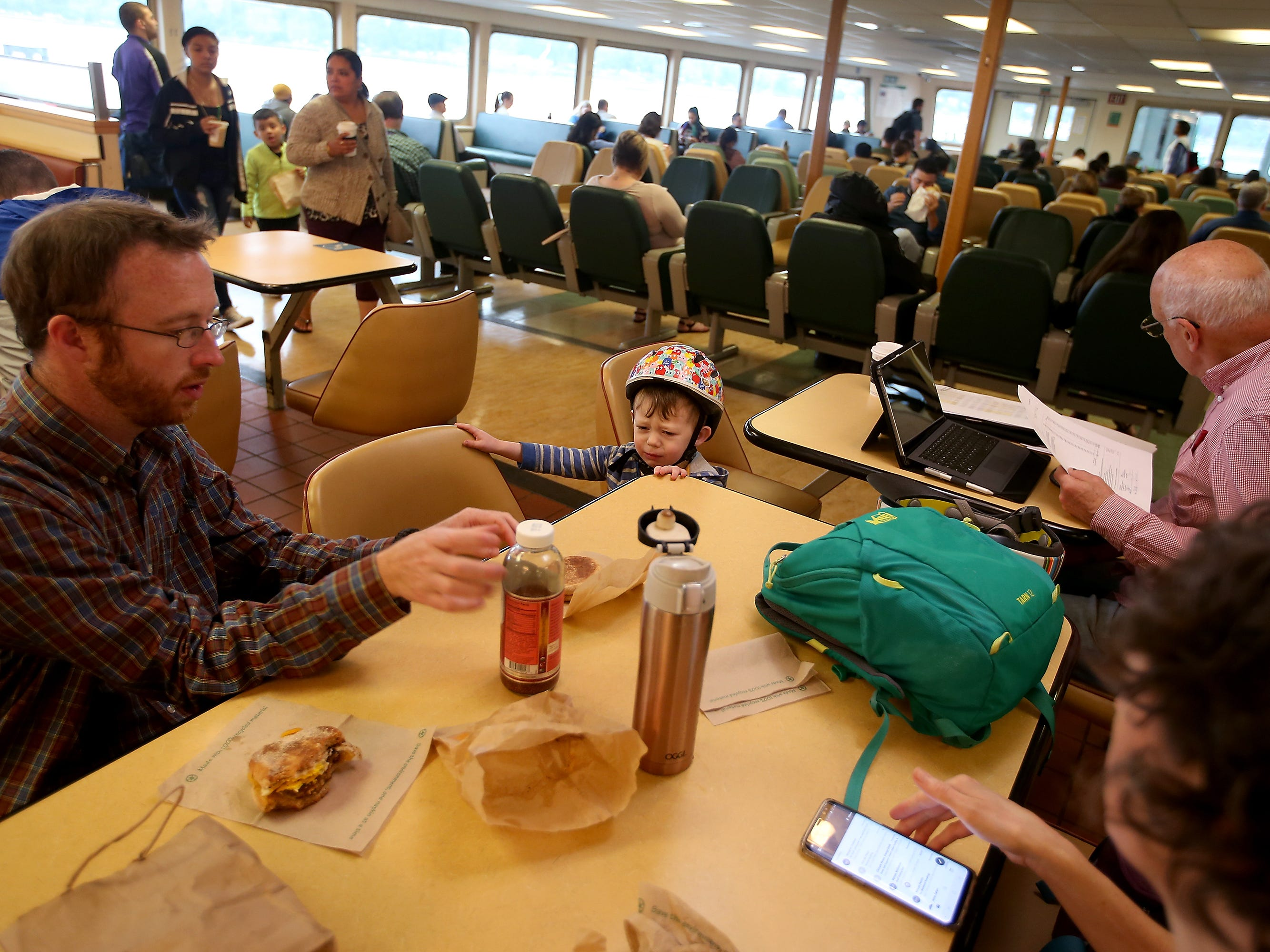 A very tired and slightly cranky Kellas MacPherson, 2, (center) reluctantly takes his seat as his father Gavin (left) and mother Aven Frey (right) get their breakfast sandwiches out, aboard the Washington State Ferry Walla Walla on Thursday, July 19, 2018. The trio commutes to work and daycare in Seattle from Bremerton.