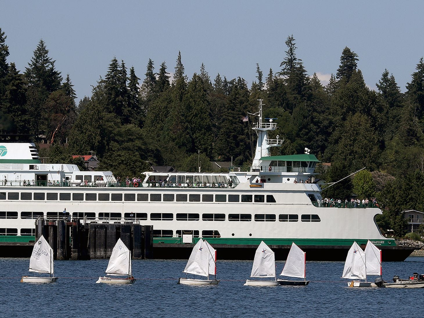 The Washington State Ferry Wenatchee moves past a line of small sailboats in Bainbridge Island's Eagle Harbor on Friday July 20, 2018.