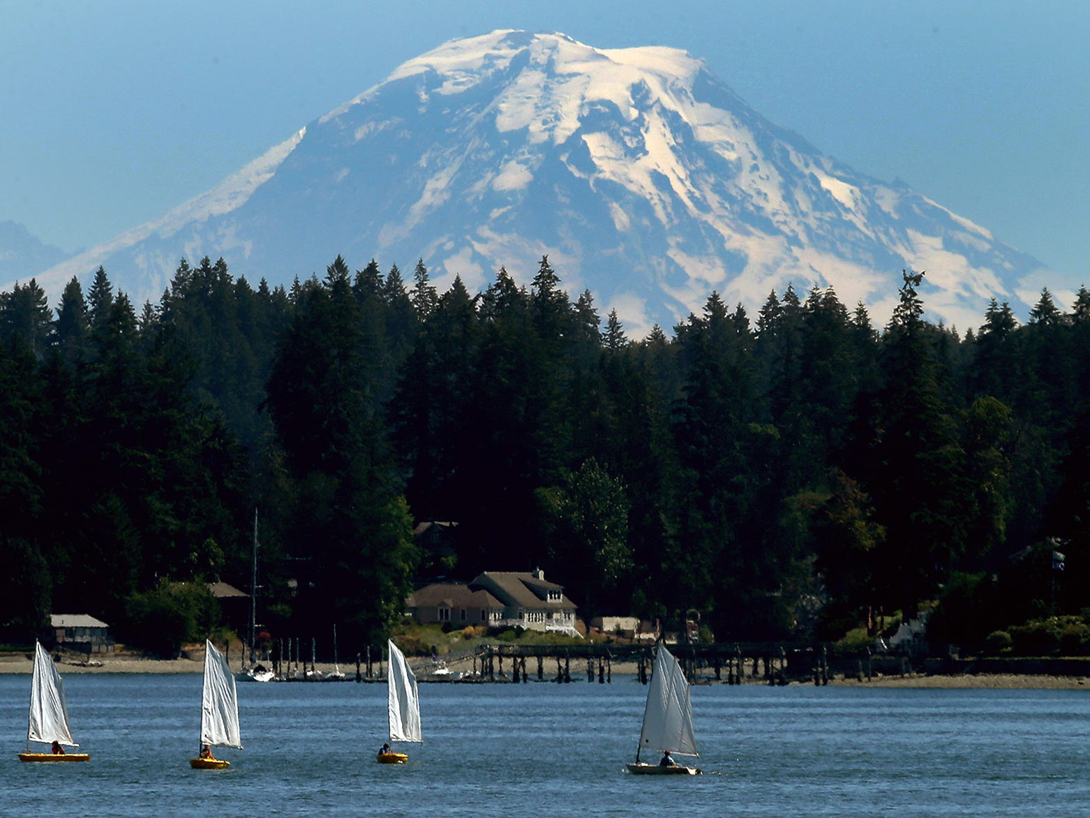 Mount Rainier looms in the distance as boats from the summer youth sailing class catch the wind on Liberty Bay in Poulsbo on Thursday, July 12, 2018.