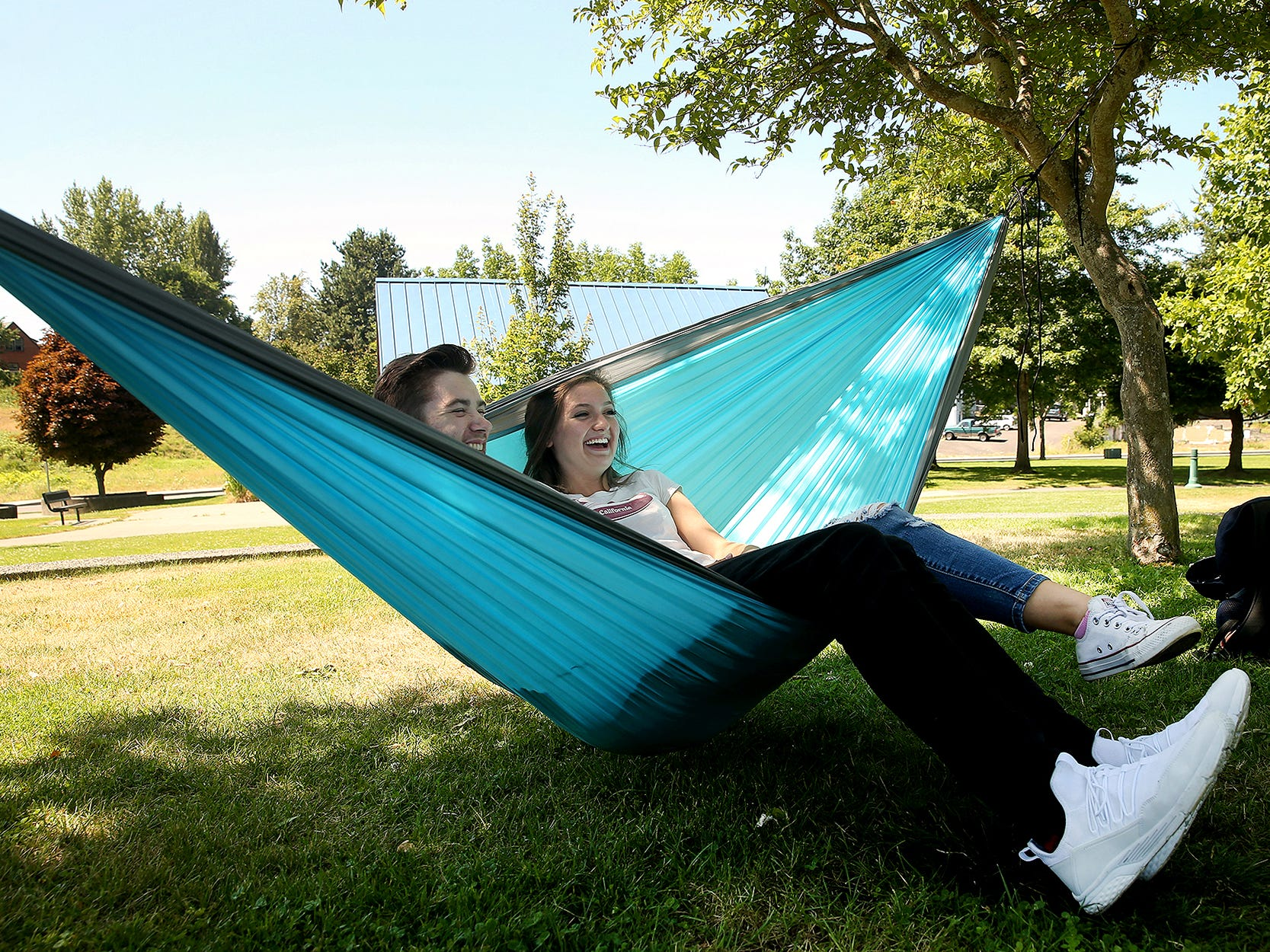 Cole Eckert, of Bremerton and Amelia Boyle, of Silverdale, relax on a hammock in the shade at Evergreen-Rotary Park in Bremerton on Tuesday.