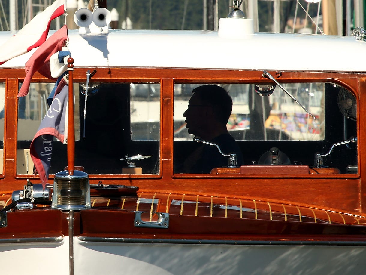 """Jim Paynton is silhouetted in the window of his 1940 42-foot Chris-Craft Double Cabin Enclosed Bridge Cruiser named """"Maranee"""" as he registers participant boaters during the annual Chris-Craft Rendezvous Chris-Craft Rendezvous at the Port Orchard Marina on Friday, July 13, 2018."""