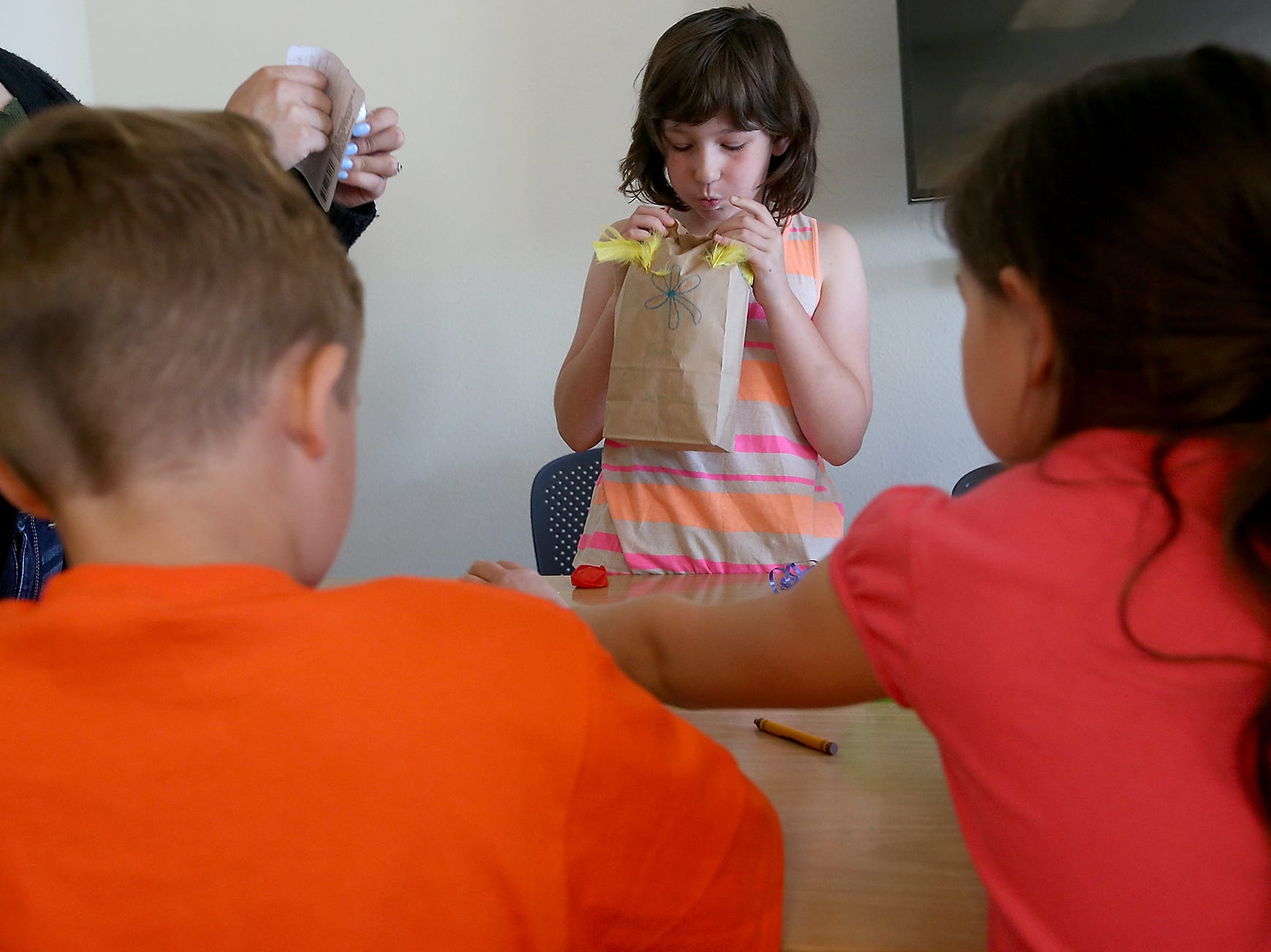 """Sahda Walker, 9, blows into a paper bag to inflate it while making a paper bag lantern with a battery operated candle inside during Ruth Carlson's Spanish Immersion """"Story Time"""" at the Port Orchard Library on Monday, July 23, 2018."""
