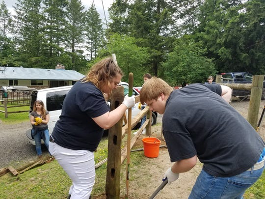 YouthBuild Kitsap students Jasmine Murphy and DJ Crow work to build a fence at One Heart Wild Education Sanctuary in Silverdale.