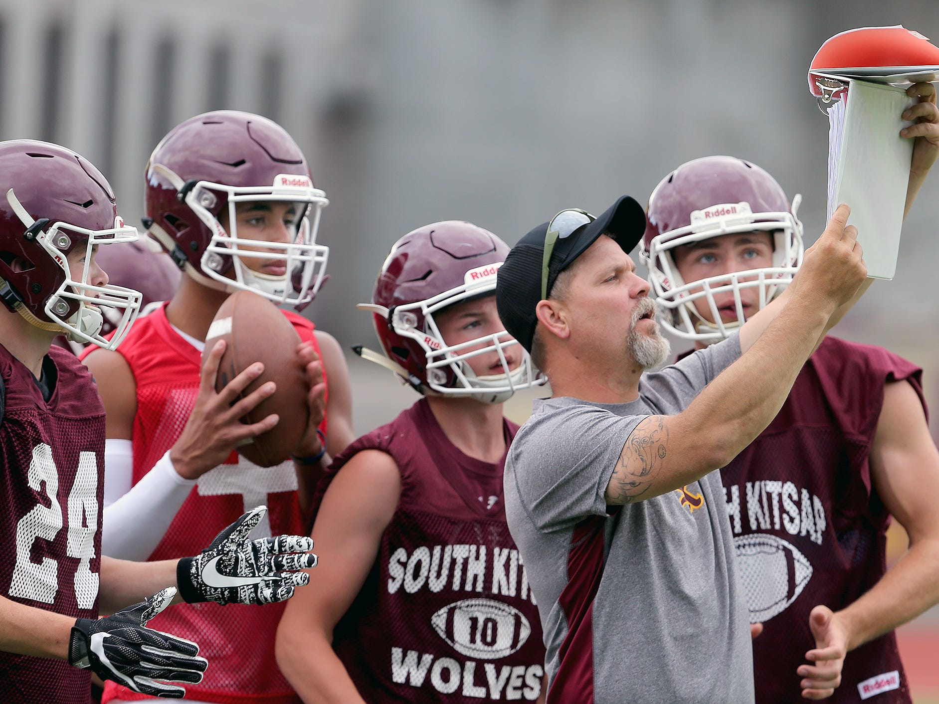 South Kitsap coach Tyler George shows offensive plays during the 7 on 7 football at South Kitsap High School in Port Orchard on Wednesday, July 18, 2018.