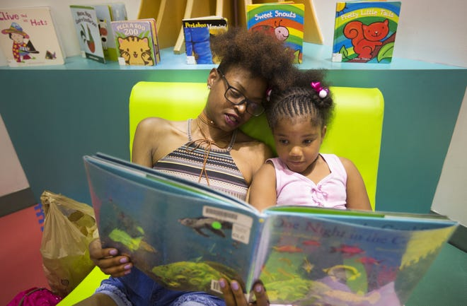 Krystal Washington, of downtown, and her daughter, McKenzie Williams, read a book together in The Children's Learning Center in the Hamilton County Public Library in downtown Cincinnati. Enquirer File