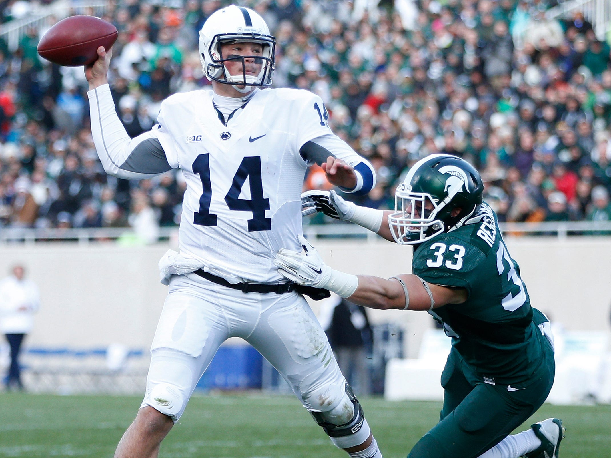 EAST LANSING, MI - NOVEMBER 28: Christian Hackenberg #14 of the Penn State Nittany Lions passes while under pressure from Jon Reschke #33 of the Michigan State Spartans in the first half of the game at Spartan Stadium on November 28, 2015 in East Lansing, Michigan.