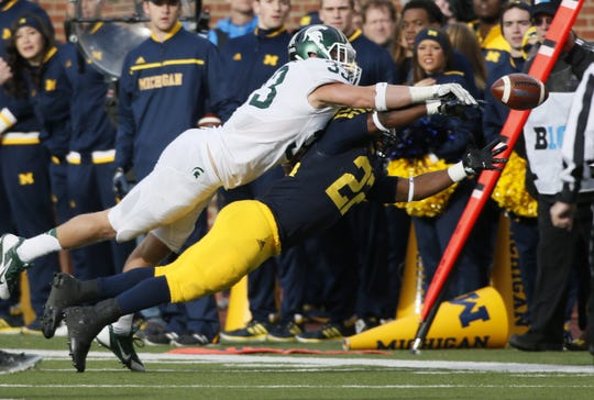 Michigan State's Jon Reschke, top, breaks up a pass to Michigan's Karan Higdon in the second quarter on Saturday, Oct. 17, 2015, at Michigan Stadium in Ann Arbor, Mich.