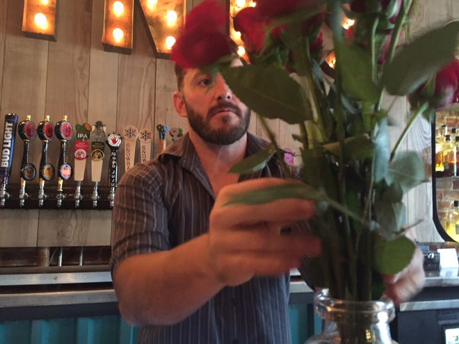 Pour Brothers bartender Tyler Davis adjust a vase of red roses during the bar's watch party Monday night.