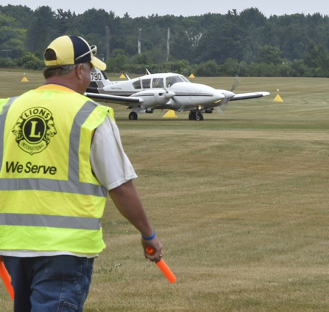 A Washington Island Lions Club volunteer guides a plane on the Saturday. During any other year, Washington Island Airport is the smallest publicly-owned grass airport in the world to host more than 100 airplanes for the longest-running fly-in on the third Saturday in July.  For more photos, visit doorcountyadvocate.com.