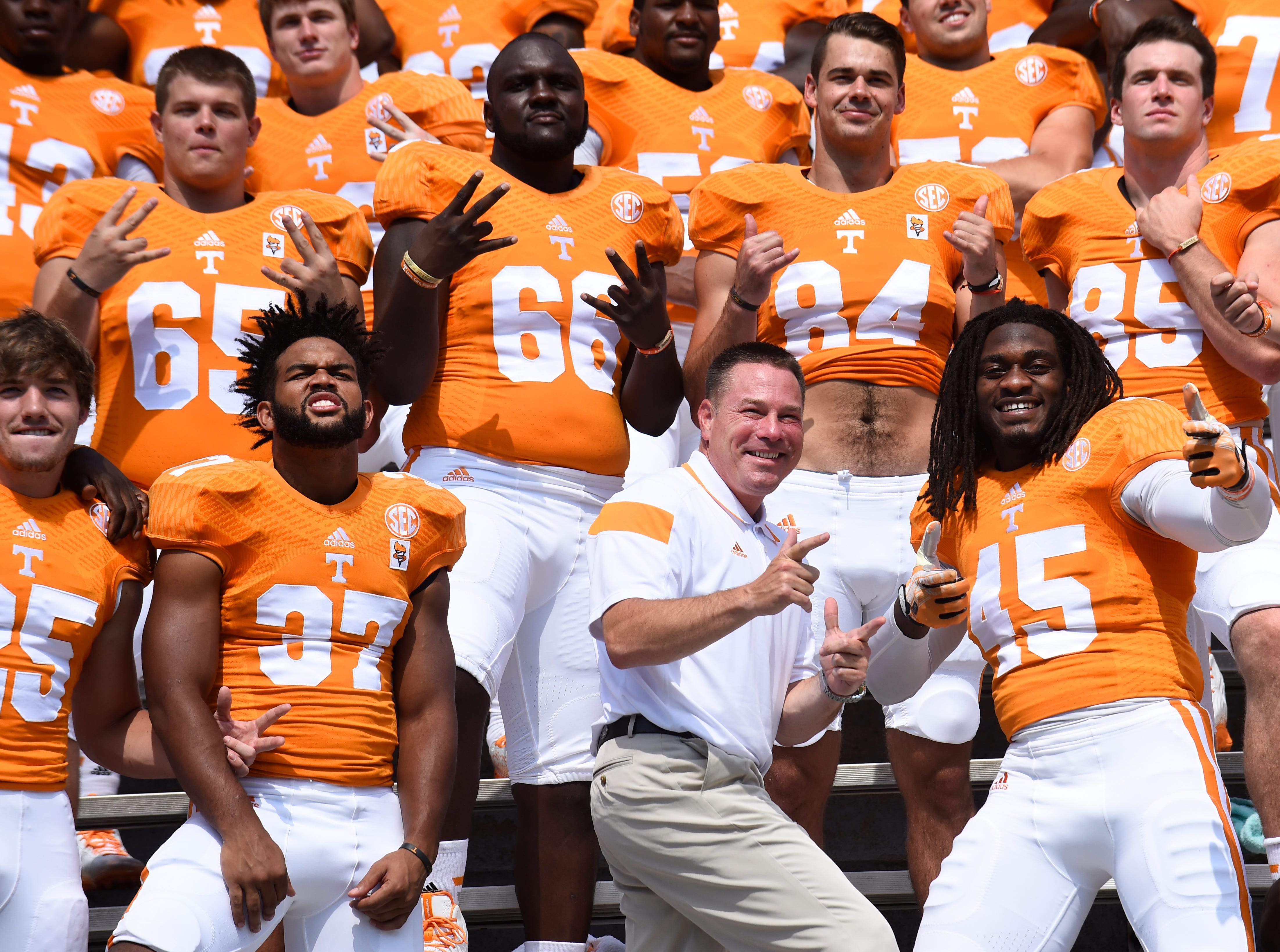 University of Tennessee head football coach Butch Jones, center, poses with players during the team photo, left is Brian Randolph, right is A.J. Johnson, during media day at Neyland Stadium Thursday, Aug. 14, 2014.