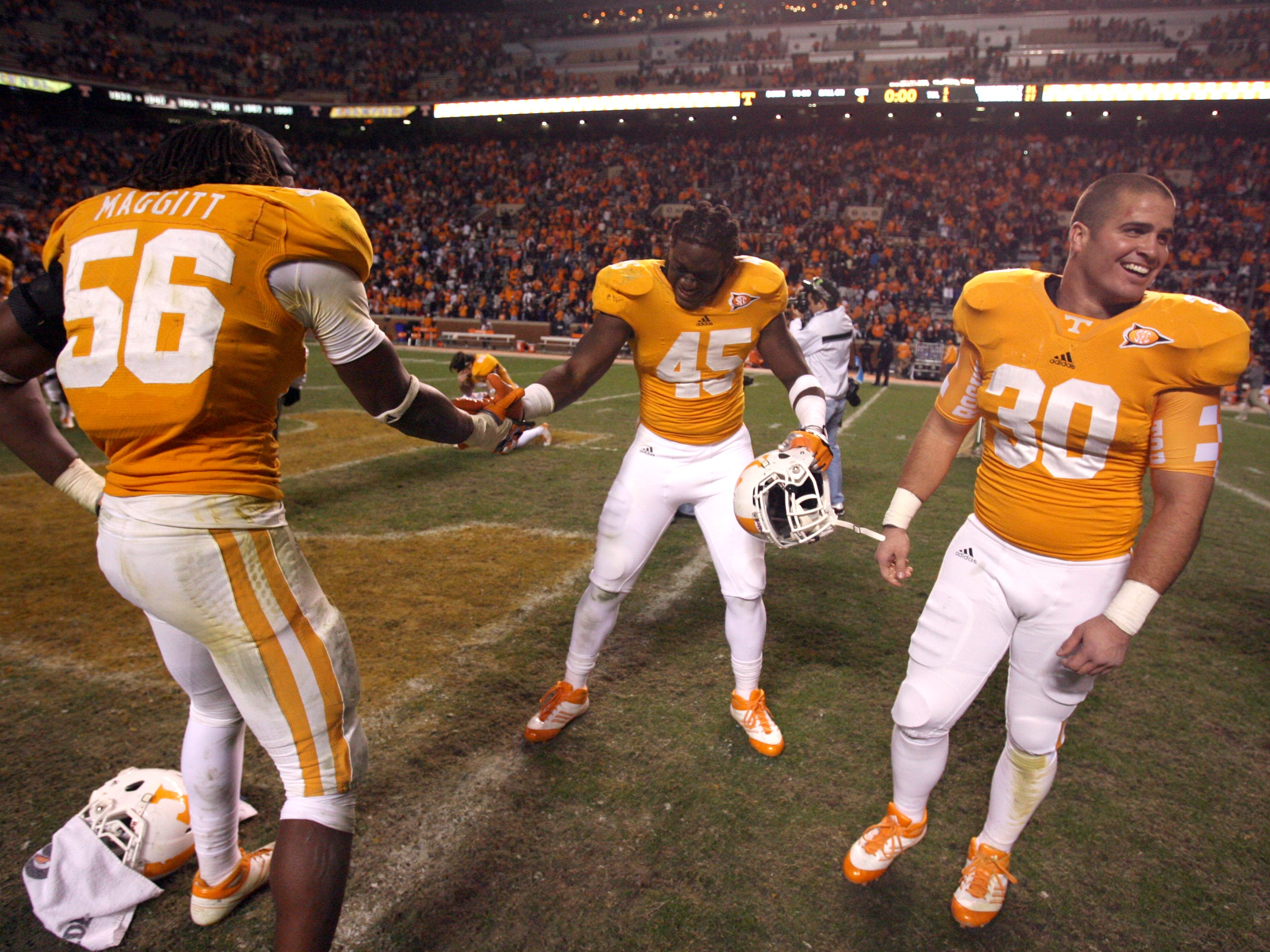 Tennessee defensive lineman Curt Maggitt (56), linebacker A.J. Johnson (45) and linebacker Shane Reveiz (30) celebrate with one another after defeating Vanderbilt 27-21 in overtime at Neyland Stadium Saturday, Nov. 19, 2011.