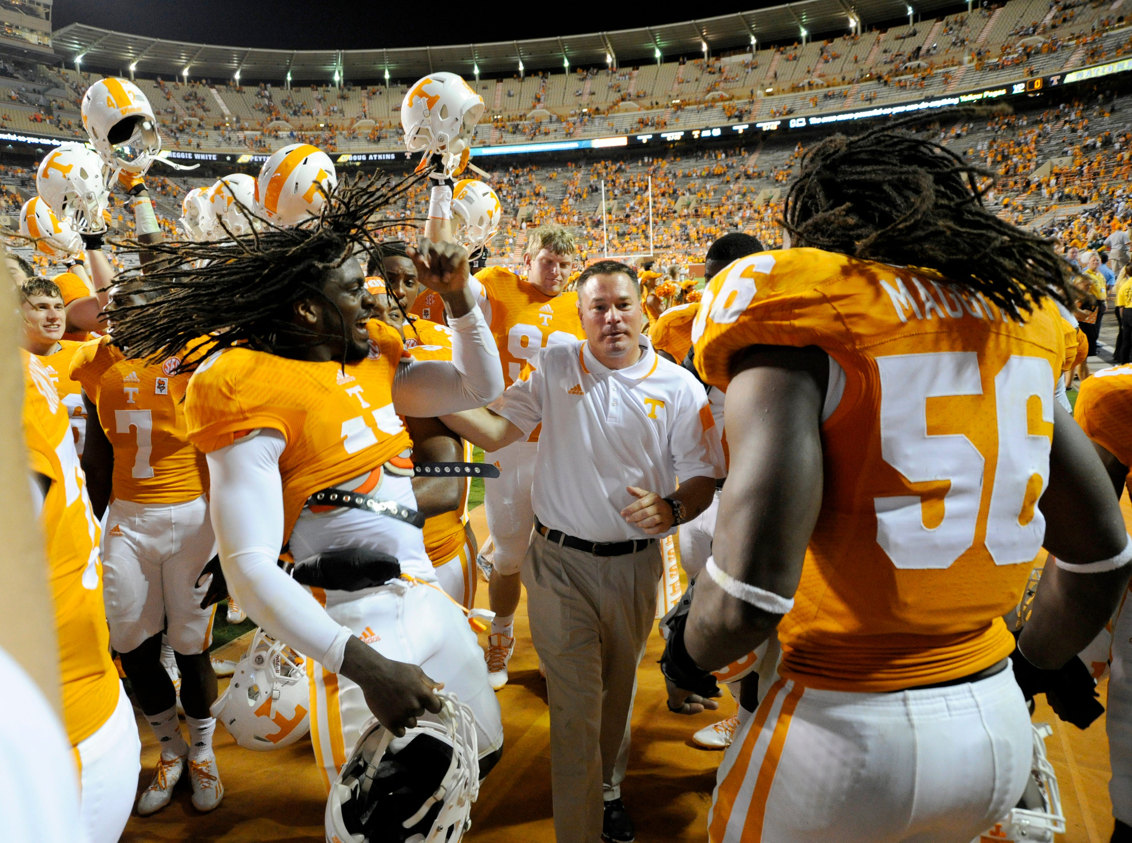 Tennessee coach Butch Jones grabs linebacker A.J. Johnson (45) and tells him to go up on the ladder with drum major and lead the band after their 38-7 victory over Utah State at Neyland Stadium, Sunday, Aug. 31, 2014 in Knoxville, Tenn.