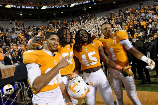Tennessee defensive back Geraldo Orta (26), linebacker Curt Maggitt (56), linebacker A.J. Johnson (45), and quarterback Joshua Dobbs (11), from left, pose for a photo while celebrating their 50-16 win over Kentucky at Neyland Stadium, Saturday, Nov.15, 2014 in Knoxville, Tenn.