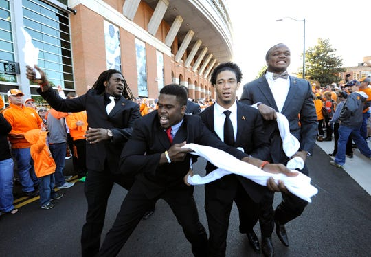 Tennessee linebacker A.J. Johnson (45), linebacker Justin King (38), defensive back Geraldo Orta (26), and linebacker Curt Maggitt (56), from left, rally the crowd gathered for the Vol Walk before the game against Florida at Neyland Stadium on Saturday, Oct. 4, 2014 in Knoxville, Tenn.