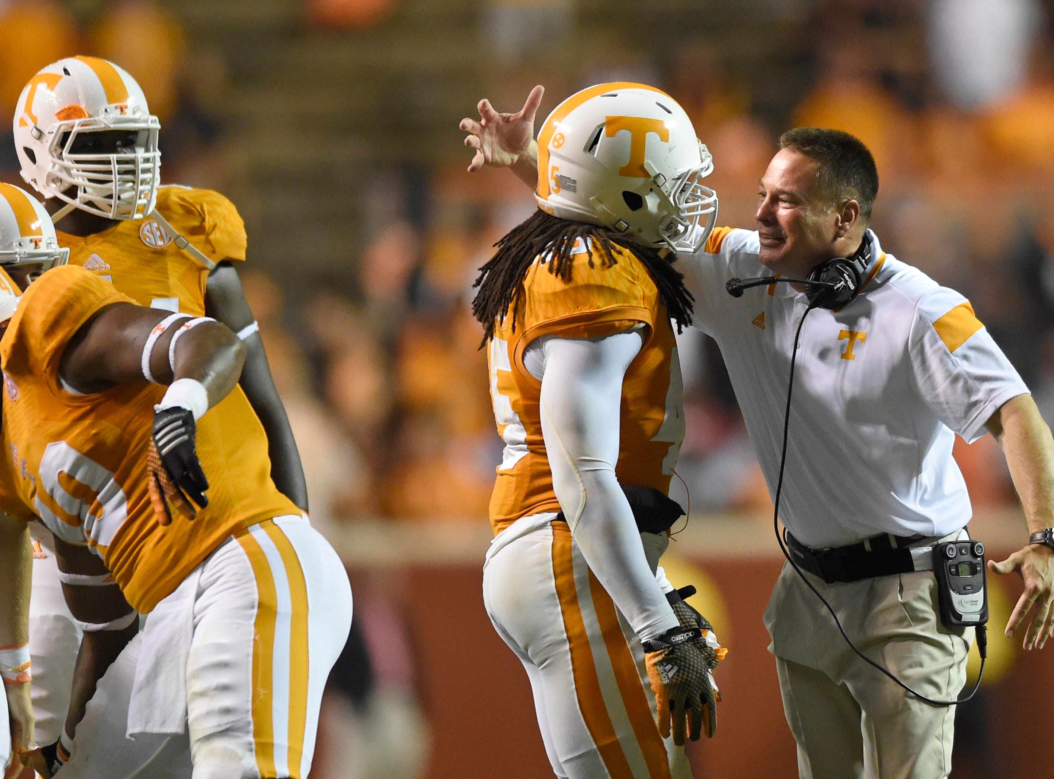Tennessee coach Butch Jones, right, embraces Tennessee linebacker A.J. Johnson (45) after Johnson made an interception against Utah State during the second half at Neyland Stadium, Sunday, Aug. 31, 2014 in Knoxville, Tenn. Tennessee won 38-7.