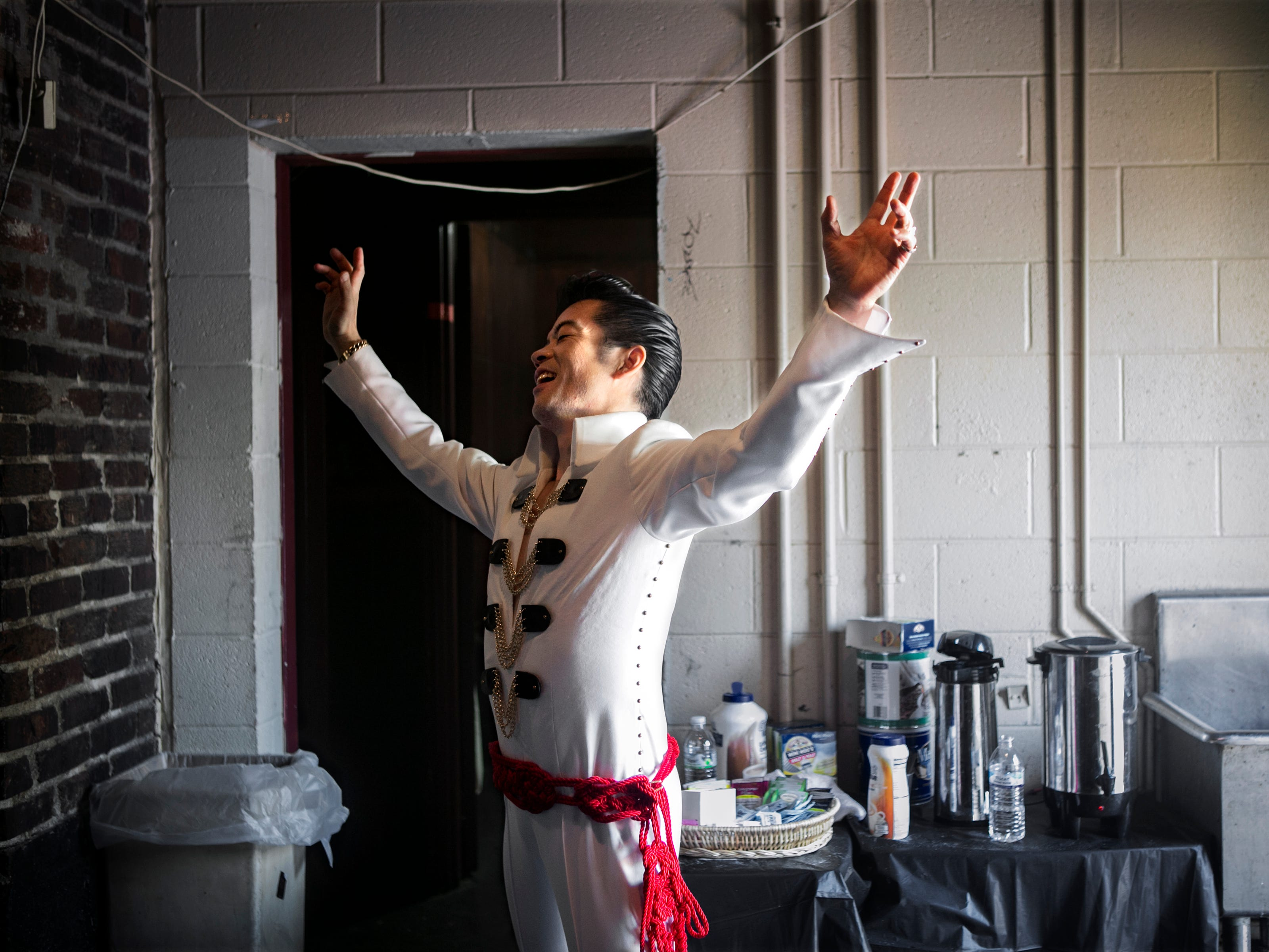 "August 15, 2014 - Elvis Presley tribute artist Charlie Neishio, 51, of Osaka, Japan, throws his arms into the air as another artist performs onstage during Doc Franklin's Original Images of the King, an Elvis Tribute Artist Contest and Showcase, at the New Daisy Theatre Friday afternoon. In 2012, Neishio won a Japanese Elvis competition and made the pilgrimage to Memphis. This year, he spent $2,600 for his flight to compete in Memphis this week. ""I love Elvis,"" Neishio states after admitting he wanted to be like the late performer since he was 14 years old. He shares that Elvis' song ""My Boy"" is a special tune that saved his life because he was a lonely child. It inspired him to sing. ""In Japan Elvis is a lot of fun,"" Neishio says. ""My hairstyle is Elvis. So, everybody likes me because (of) Elvis."" (Yalonda M. James/The Commercial Appeal)"