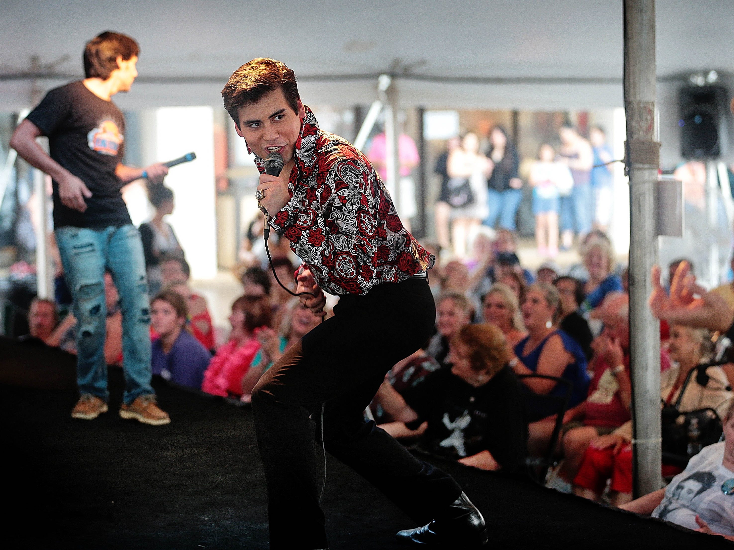 August 16, 2016 - Elvis Presley tribute artist Taylor Rodriguez (center) performs in the tent at Graceland Crossing with Cote Deonath (left) and Ben Thompson for a crowd of  Elvis fans who were still basking in the lingering Elvis aura a day after the annual vigil. (Jim Weber/ The Commercial Appeal)